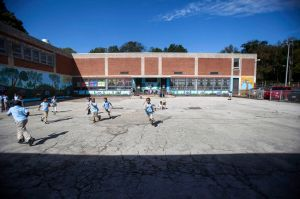 Students at recess on a patchy asphalt lot, at Anna Lane Lingelbach Elementary School in Philadelphia.